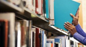 Librarian reshelving a book